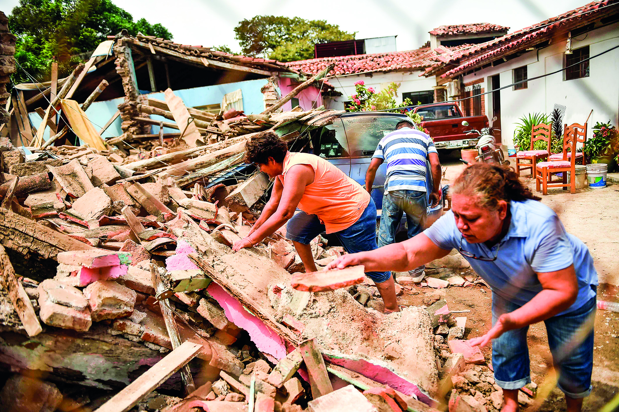 People search on September 8, 2017 amid the rubble of buildings which collapsed in Juchitan de Zaragoza, state of Oaxaca, after an 8.2 earthquake that hit Mexico's Pacific coast overnight. Mexico's most powerful earthquake in a century killed at least 35 people, officials said, after it struck the Pacific coast, wrecking homes and sending families fleeing into the streets. / AFP PHOTO / Pedro PARDO